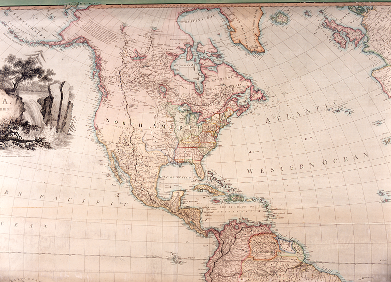 A large antique map showing North and South America and featuring a decorative illustration of a waterfall