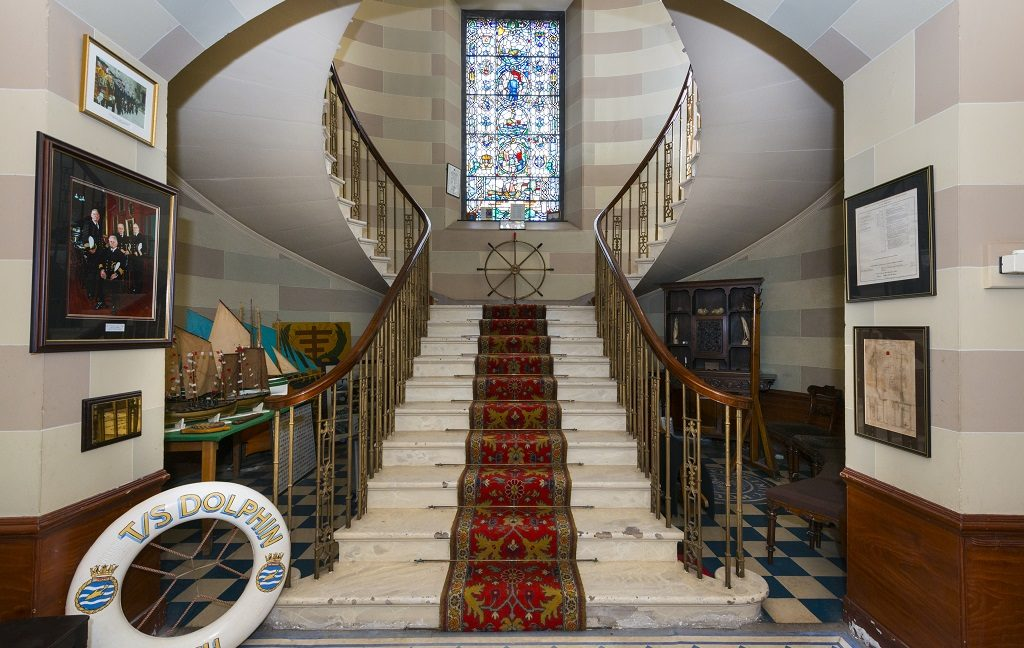 A grand staircase in Trinity House flanked by various items of maritime memorabilia