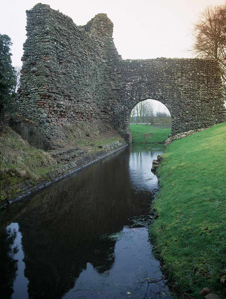 A ruined castle. An archway crosses a moat.