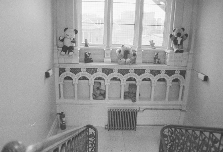 An ornate landing window with lots of teddy bears sitting on the window ledge.
