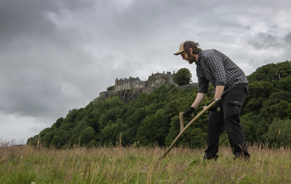man in hat and gloves carries out scything, a traditional method of grass cutting using a curved blade which dates back to ancient times