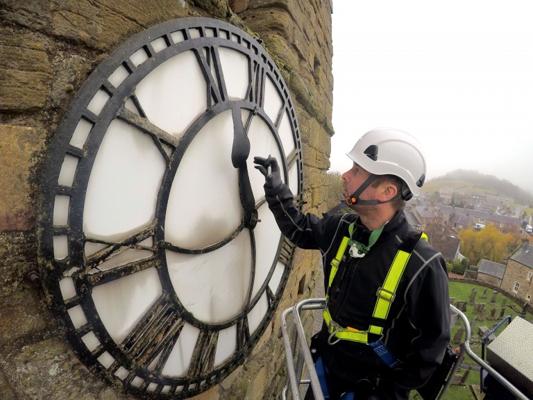 close up of a steeple clock specialist wearing hard hat and safety gear working on one of the faces of a church clock on the side of a tower