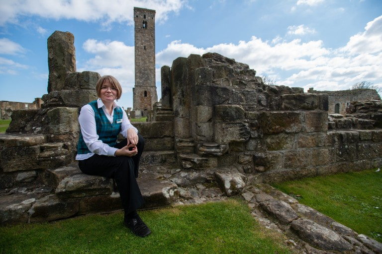 woman in white shirt, black trousers and tartan waistcoat sits on a wall with a ruined building and a tall tower visible behind her