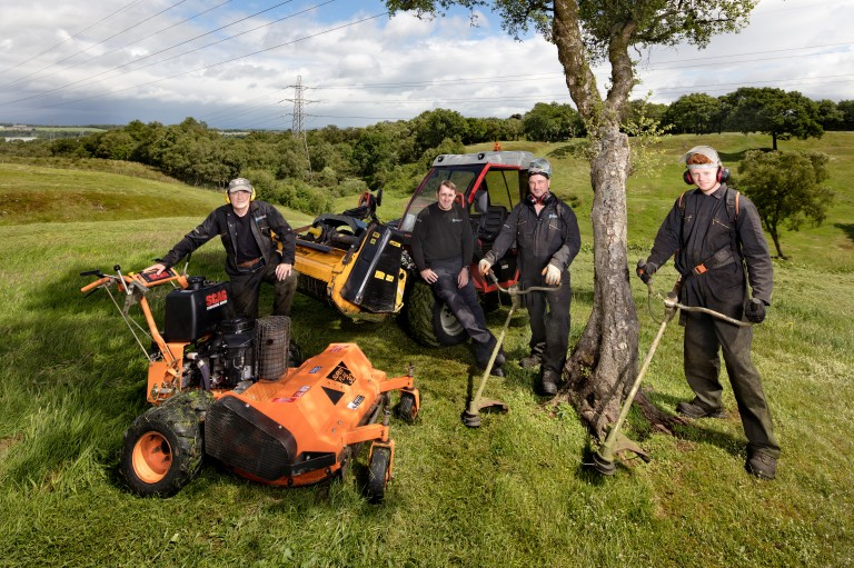four men standing by a tree holding various gardening equipment face the camera