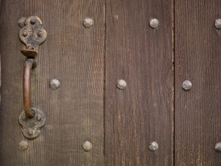 brown wooden door studded with nails