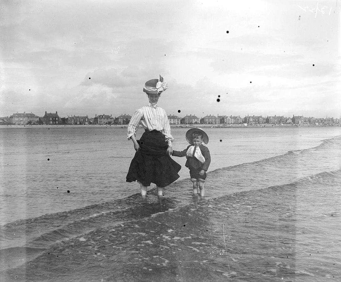 A woman and a boy stand in the sea, probably along the Clyde, in Renfrewshire in around 1900.