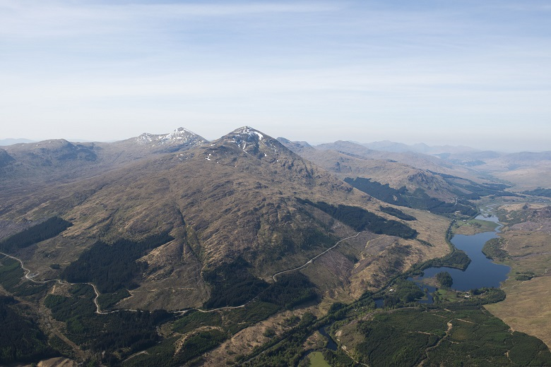 An aerial photo showing clear skies over a mountain and a loch