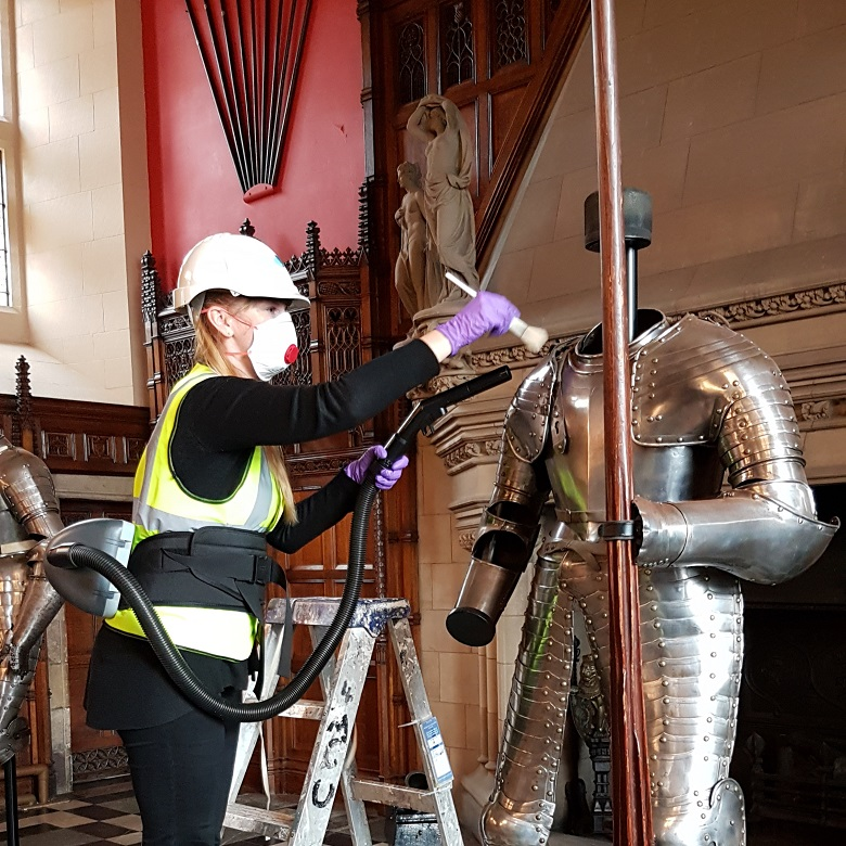 A masked and helmeted conservator cleans a suit of armour