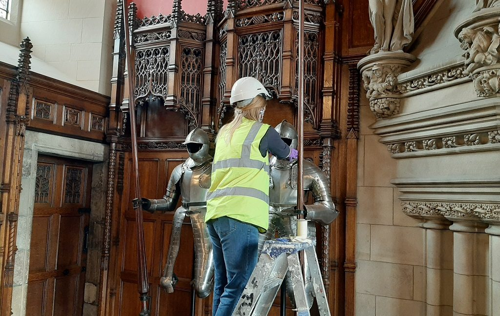 A conservator in a mask, helmet and high-vis jacket stands on a step ladder in order to clean a suit of armour