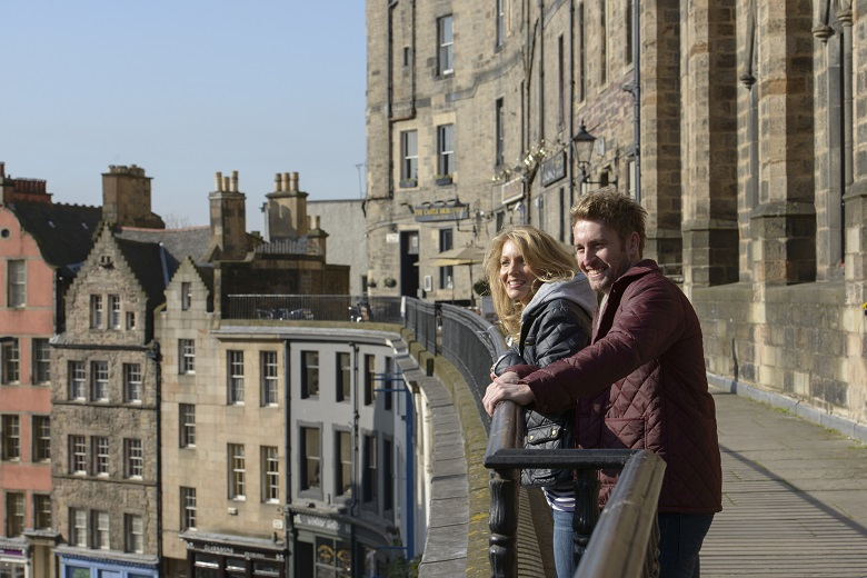 A couple smiling and laughing as they explore Edinburgh's Old Town
