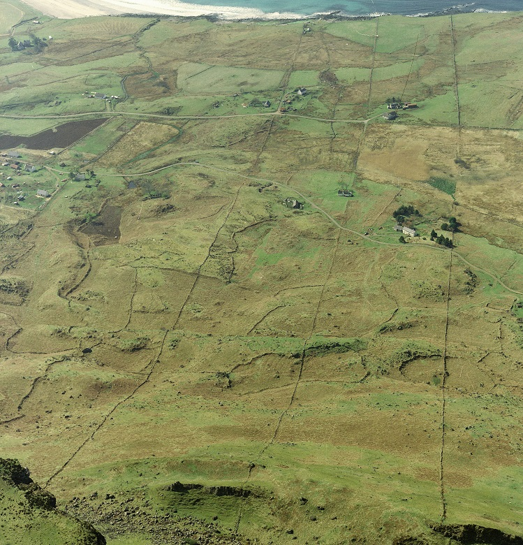 An aerial photo of green farmland divided by stone walls and other ancient markers