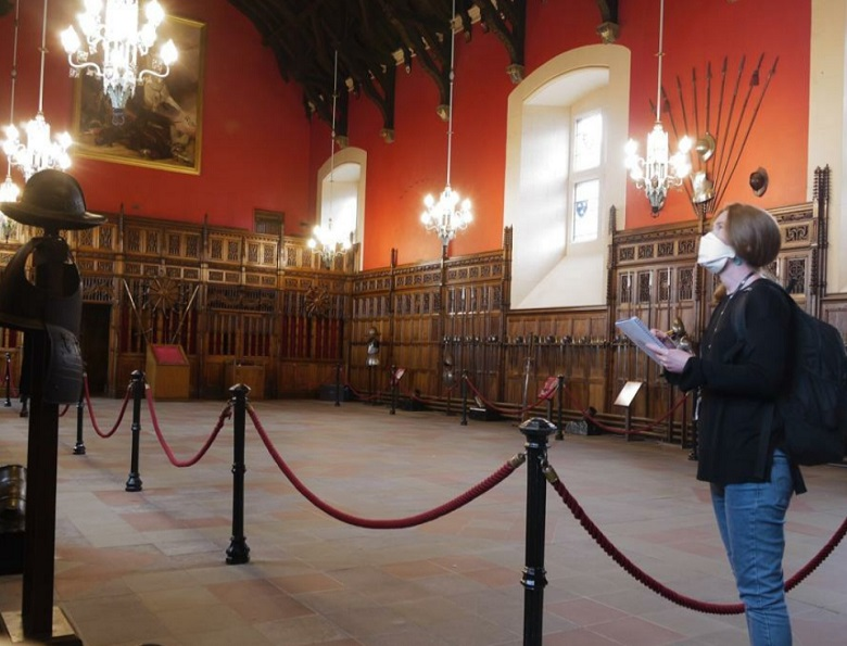 A masked conservator makes checks with a clipboard in the great hall of a castle