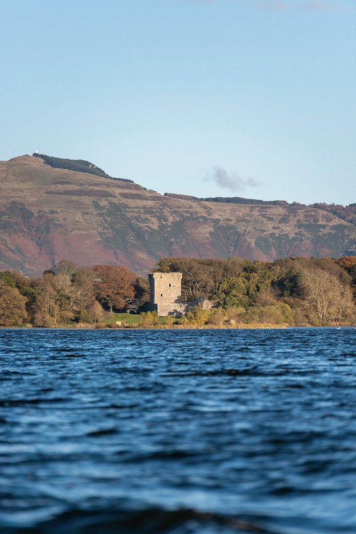 A view across a loch to the ruins of a castle on an island