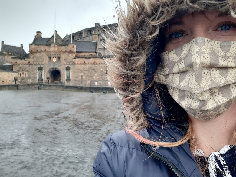 A conservator in the rain in front of Edinburgh Castle