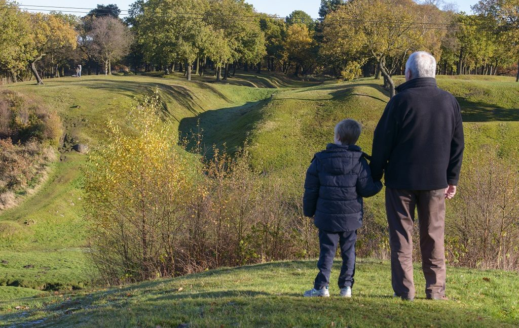 A young boy and his grandfather looking over the Antonine Wall World Heritage Site