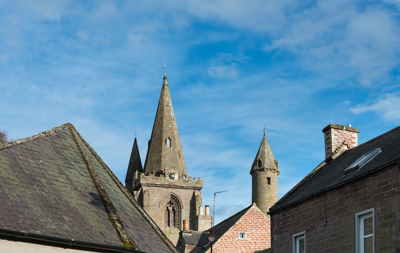 A view across the rooftops above a Scottish town featuring a church tower and a historic round tower