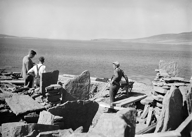 Three men stand among ruined stone walls.