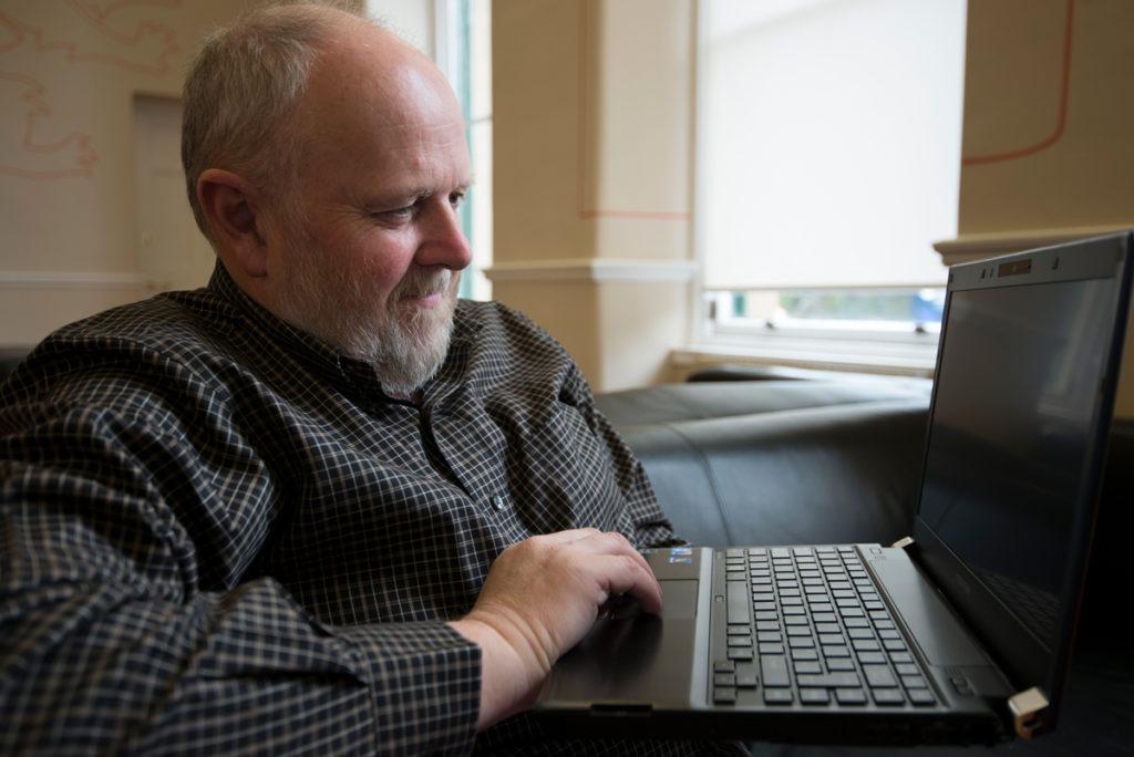 A man with a beard wearing a shirt using a laptop.