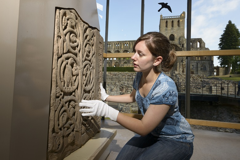 Woman wearing white cotton gloves kneels in front of a carved stone.