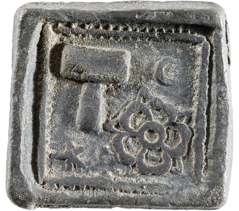 A square token with a decorative edge, featuring a rose and hammer.