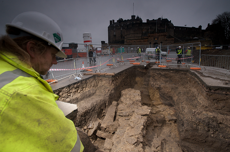 Man in a hard hat and yellow jacket views excavation trenches