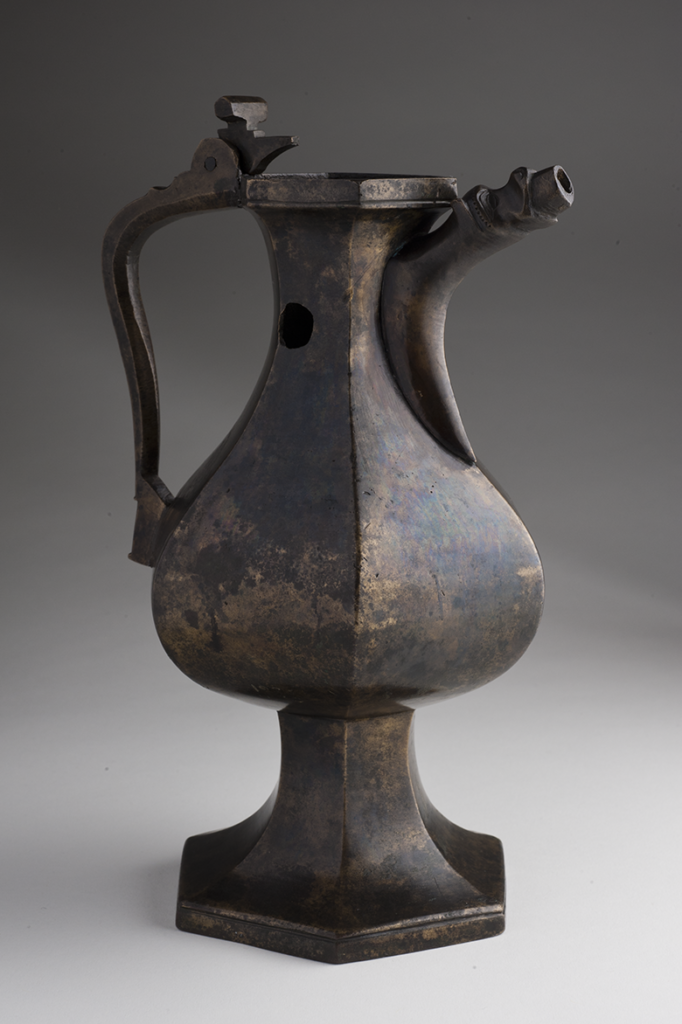 a hexagonal shaped jug with a hole in its neck