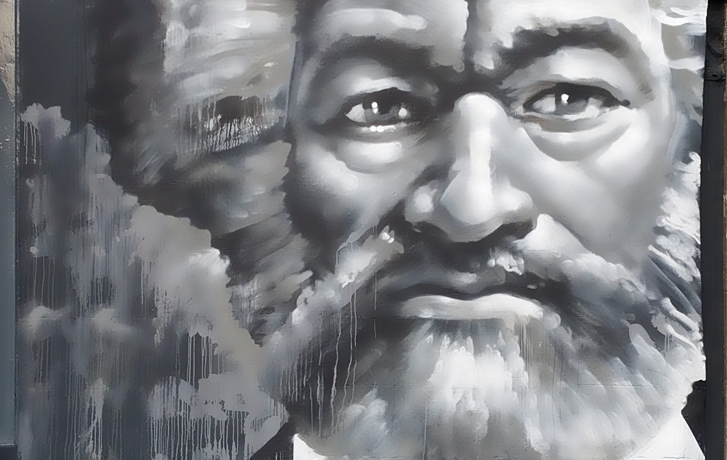 A close up of Frederick Douglass' bearded face on a mural
