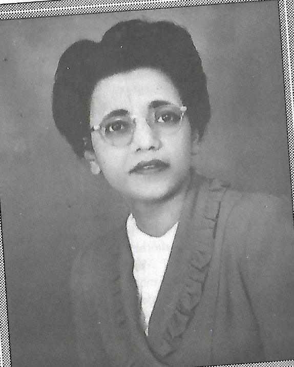 Young woman of Indian and Mauritian descent looks past the camera. She is wearing glasses and suit jacket