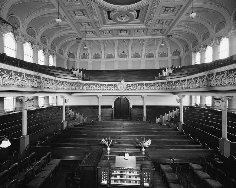 Archive photo of the ornate interior of a church with banks of pews and a gallery