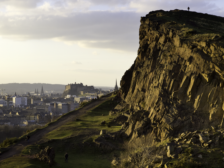 Rocky crags with the city of Edinburgh in the background