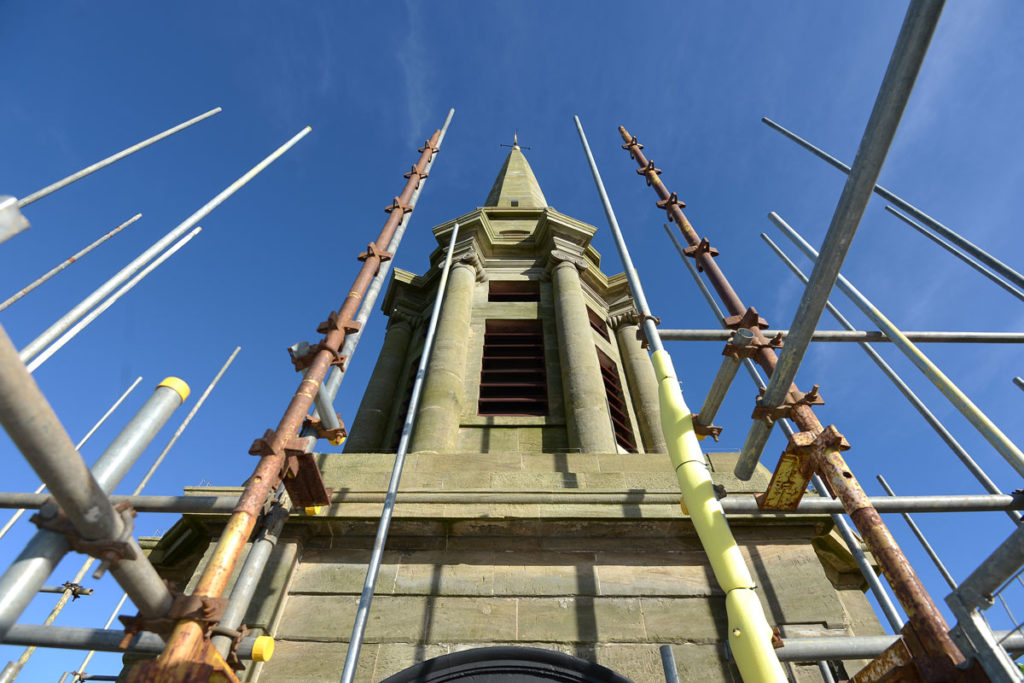 A tall building with a spire, surrounded by scaffolding