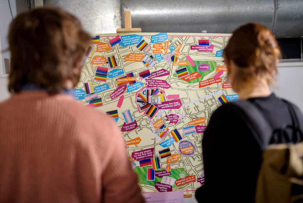 Two people look at a map annotated with events and covered in variations of the Gay Pride Rainbow Flag