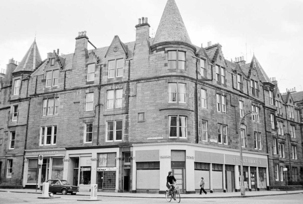 A black and white photograph of tenement buildings. A person on a bicycle cycles by.