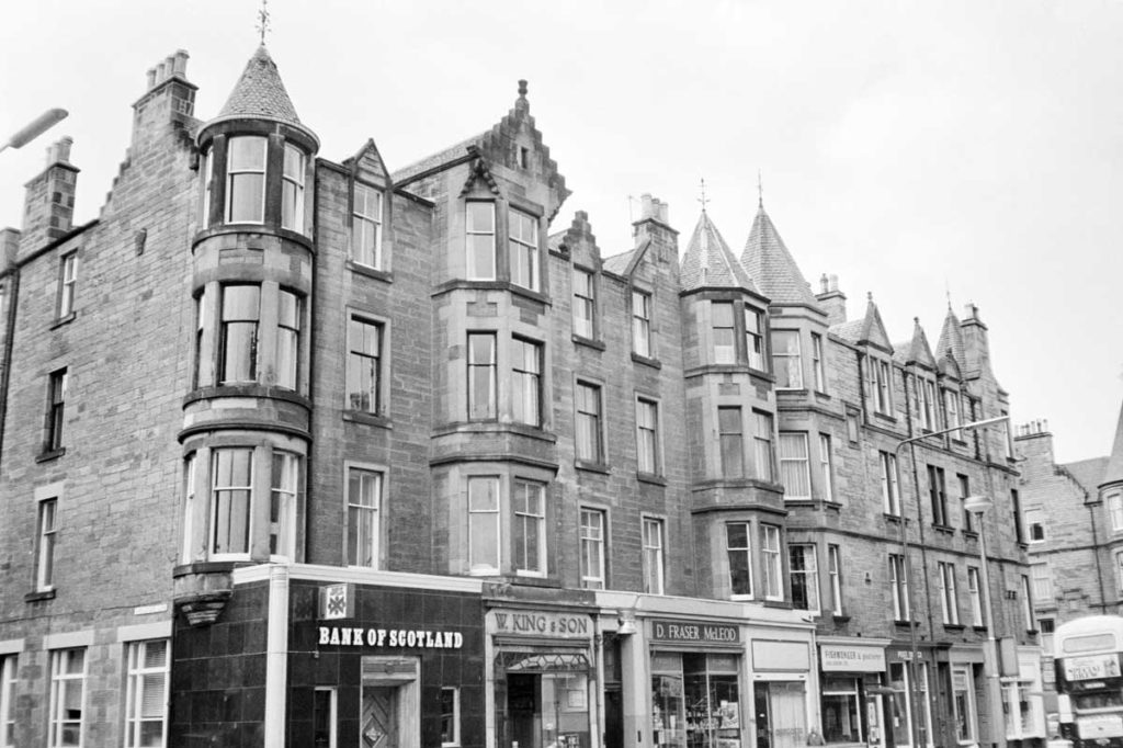 A row of tenement buildings with shops on the ground floor