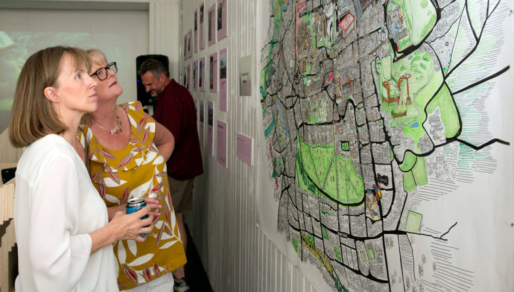 Two women look at an artistic map of Edinburgh on a wall