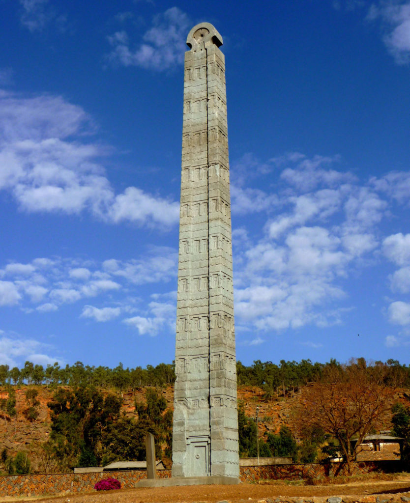 A tall stone obelisk made of carved blocks