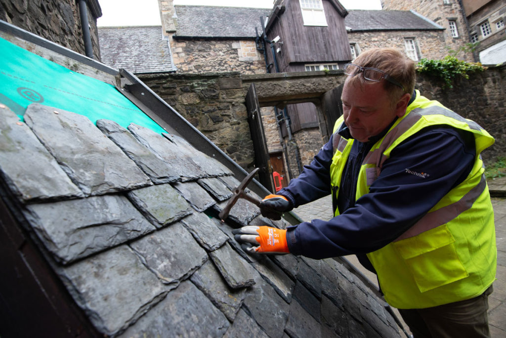 A man in a high visibility jacket and wearing gloves repairs the tiles of a roof