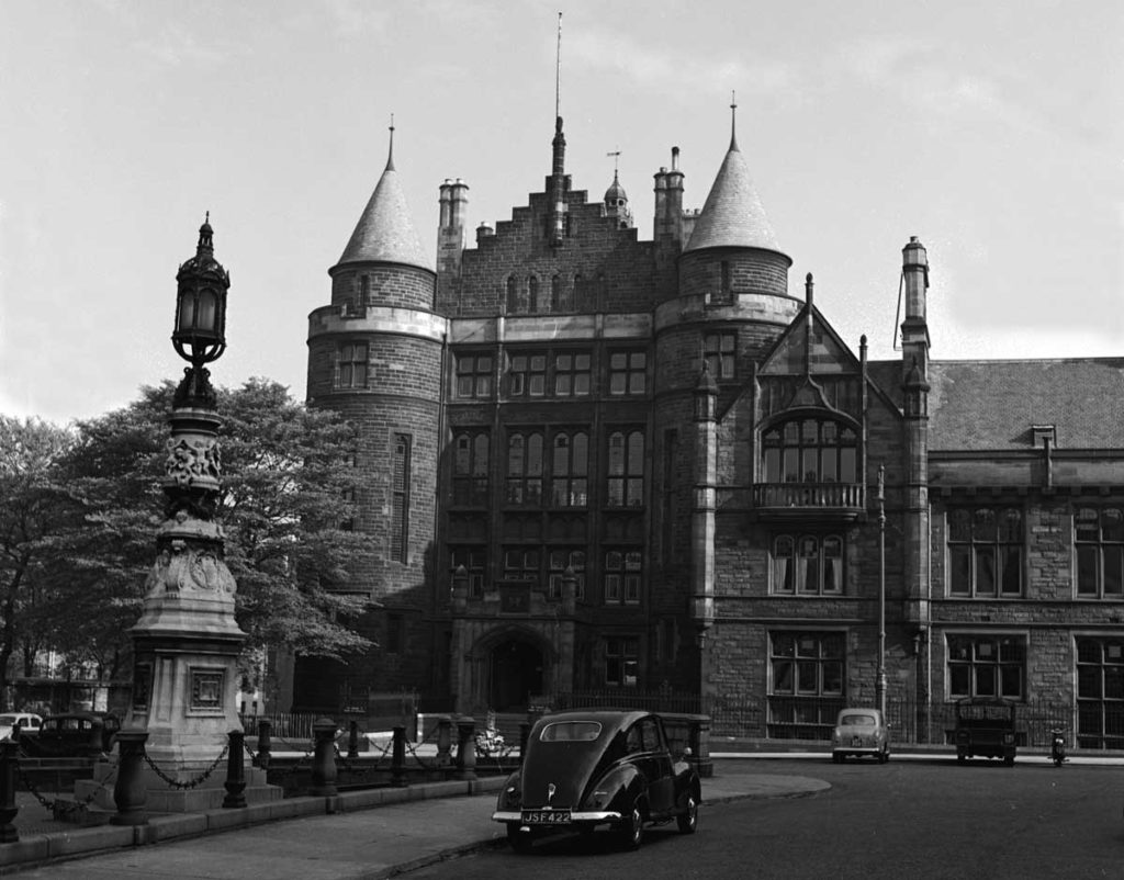 A vintage car in front of a grand, turreted building