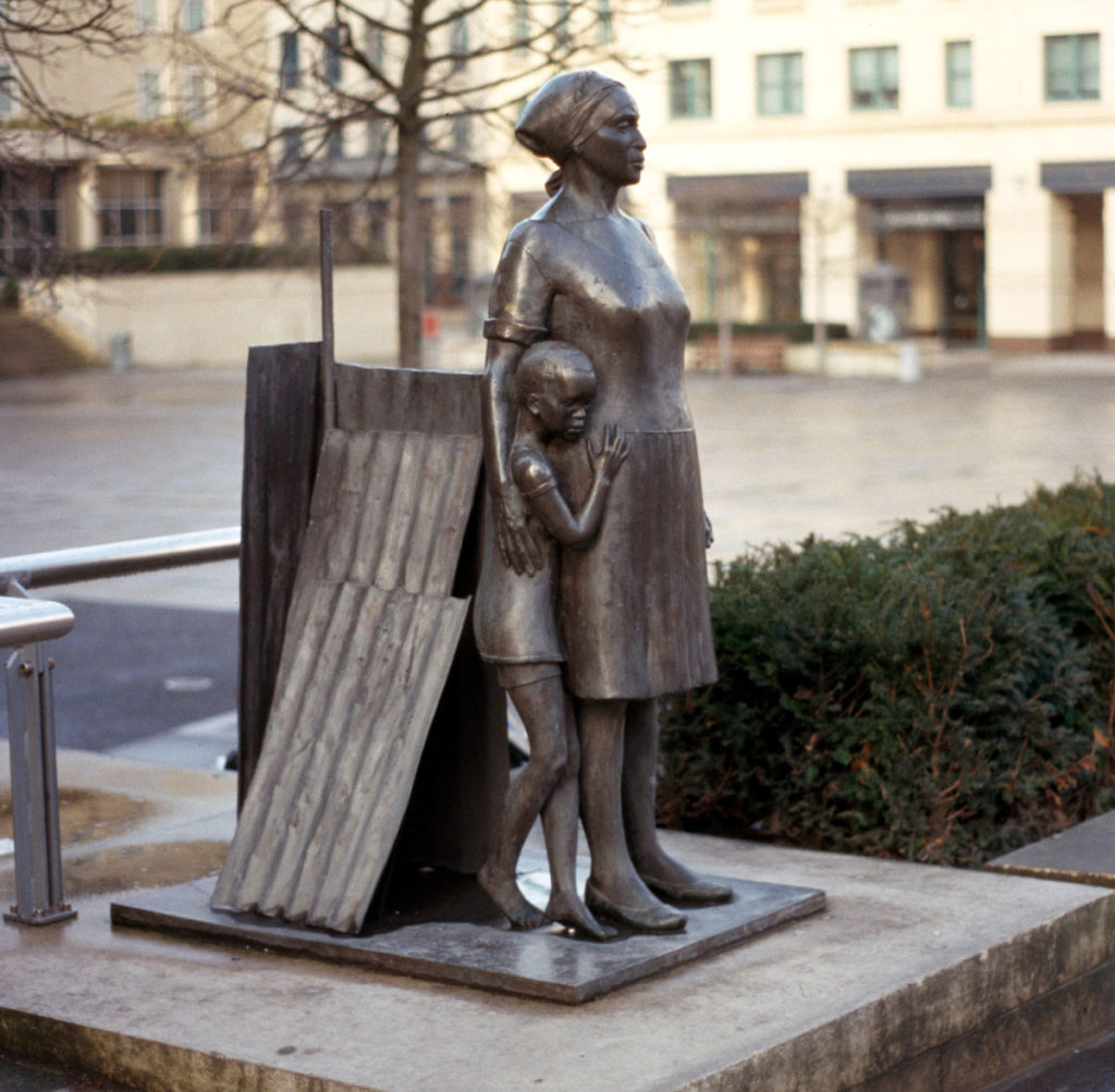 A bronze statue of a Black woman, dressed in knee-length dress, headscarf and shoes, with her right arm around a boy who cowers at her side
