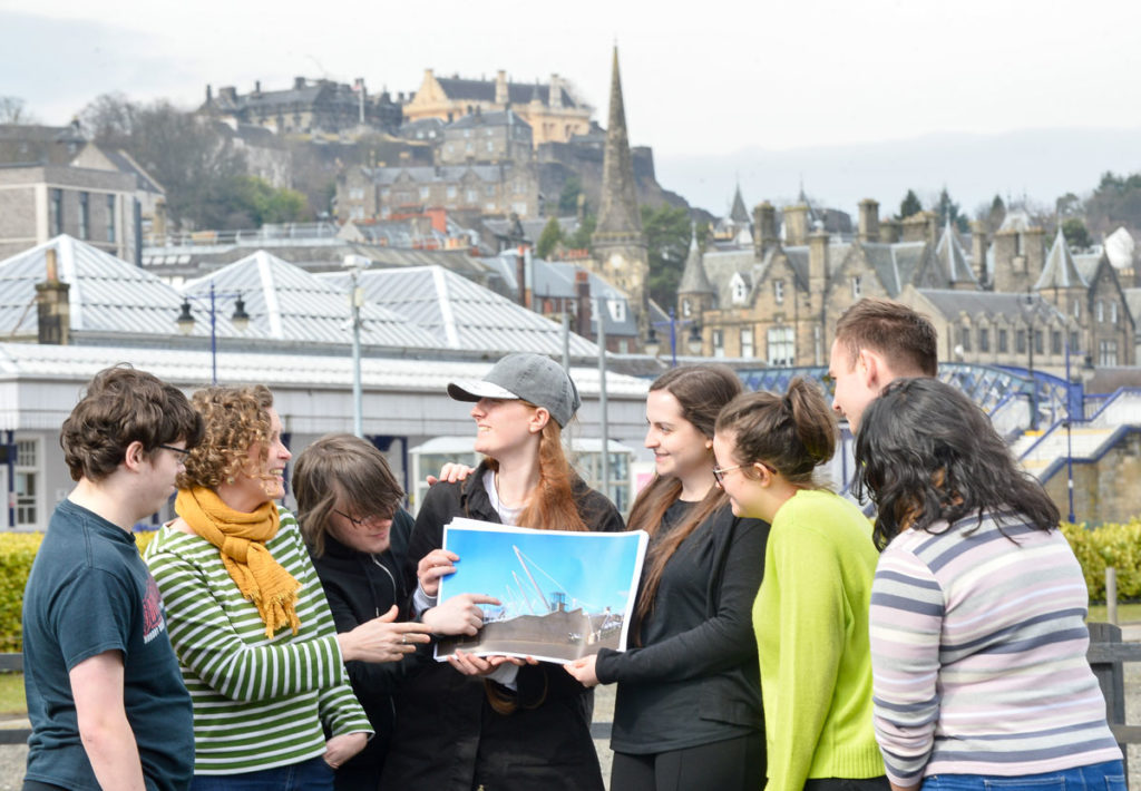 A group of young people in front of Stirling Castle looking at a photograph of an industrial crane