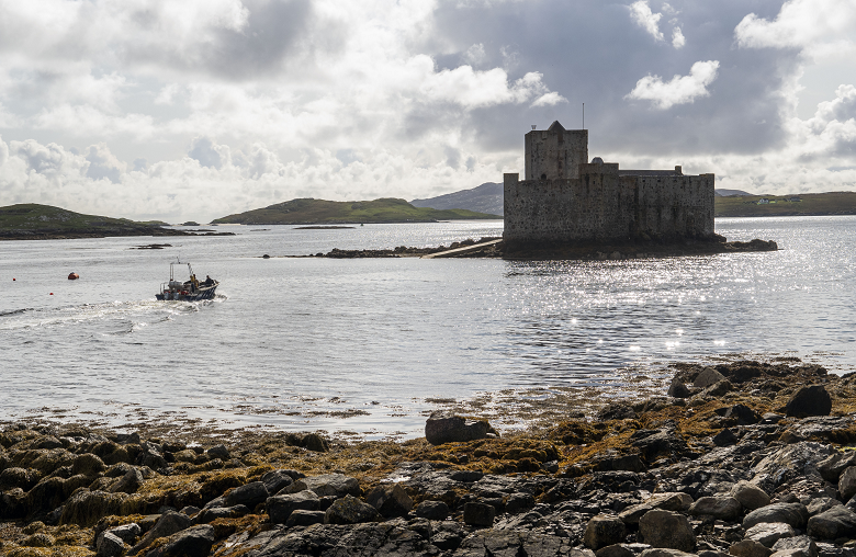 A small boat approaching a castle on an island in a bay