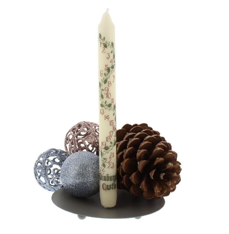 unlit candle with numbers 1-24 printed down the length of it, with a pine cone and christmas baubles at base