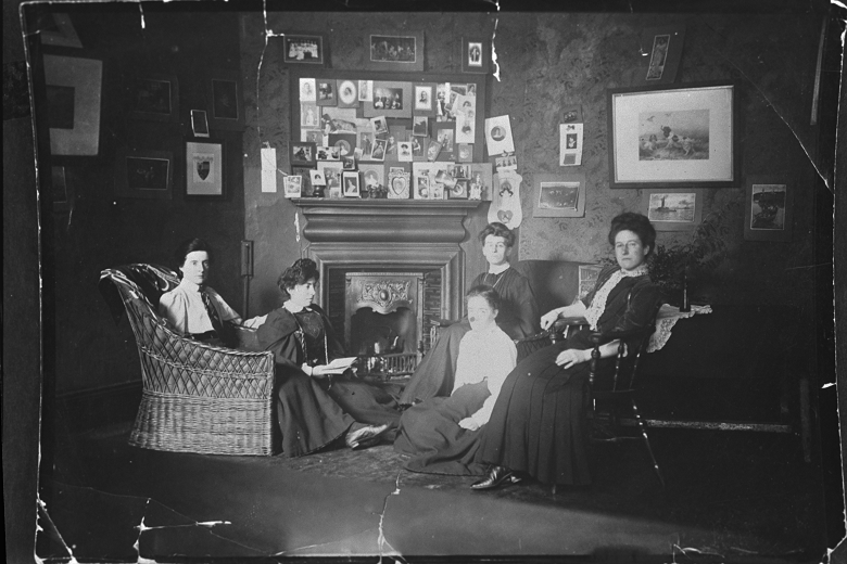 Archive photo of a group in a sitting room decorated with various cards and paintings
