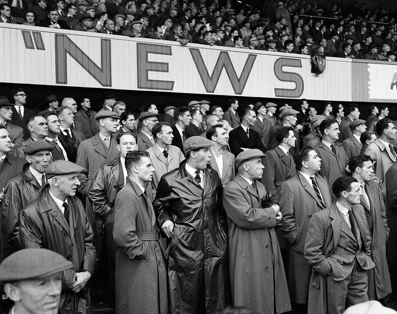 A football crowd, predominately male and flat-capped, standing under an advertising hoarding
