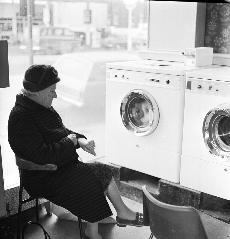 A lady checks her watch while sitting in a launderette