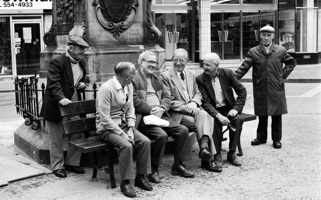Men sit and chat on bench beneath astatue of Queen Victoria