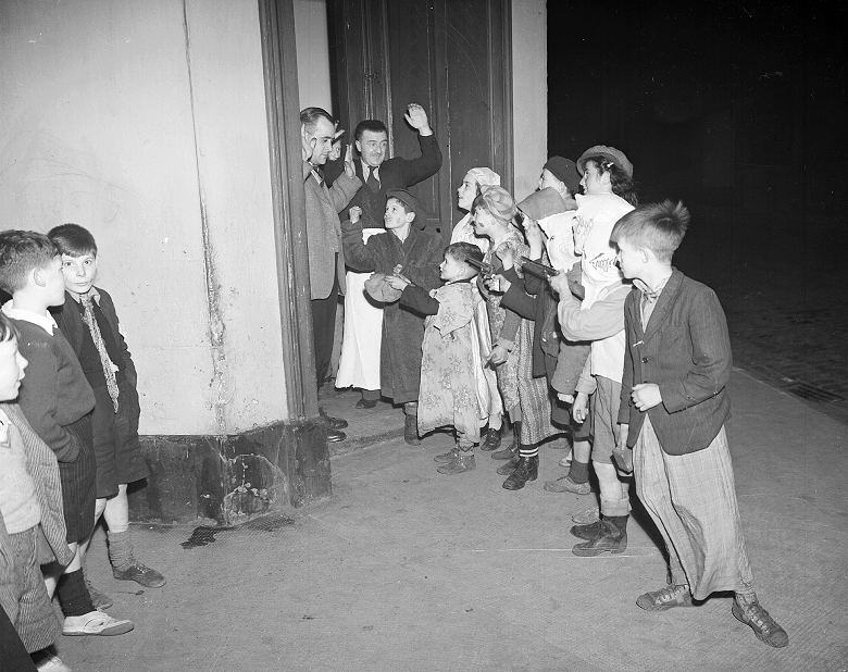 Children pretend to threaten two men who have answered their door during a evening of guising