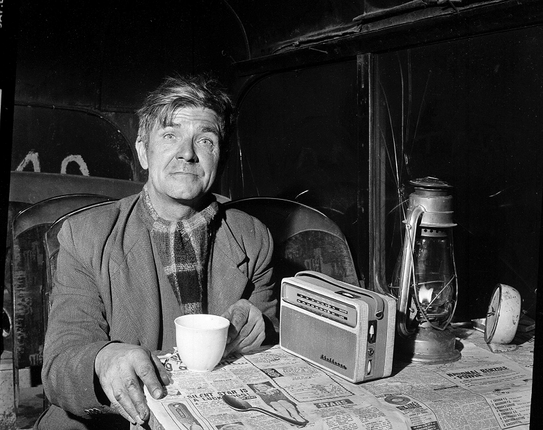 A man in a jacket and scarf poses with a hot drink, a radio and a gas lamp