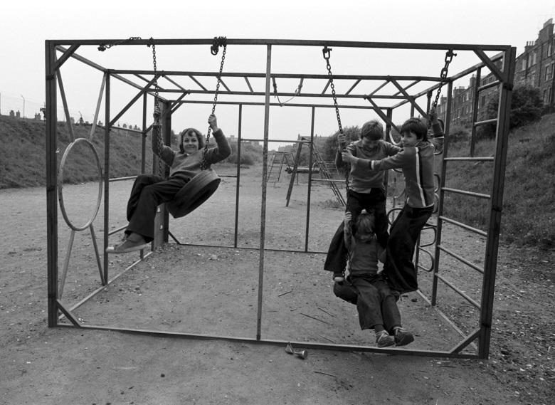 Children play on metal play equipment and swings in a play area on a disused railway line