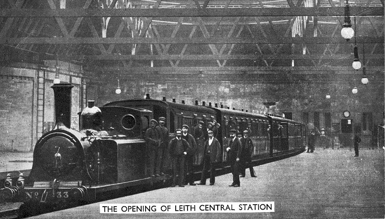 Railway workers pose in front of a stationary locomotive